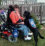 Foto de mujer con ventilación asistida y perro de asistencia